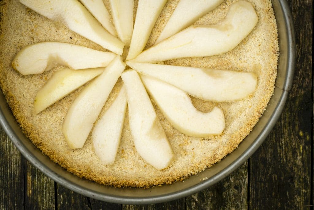 Laying pears on vegan chocolate and pear tart